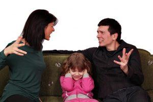 Frau und Mann streiten und Kind sitzt in der Mitte